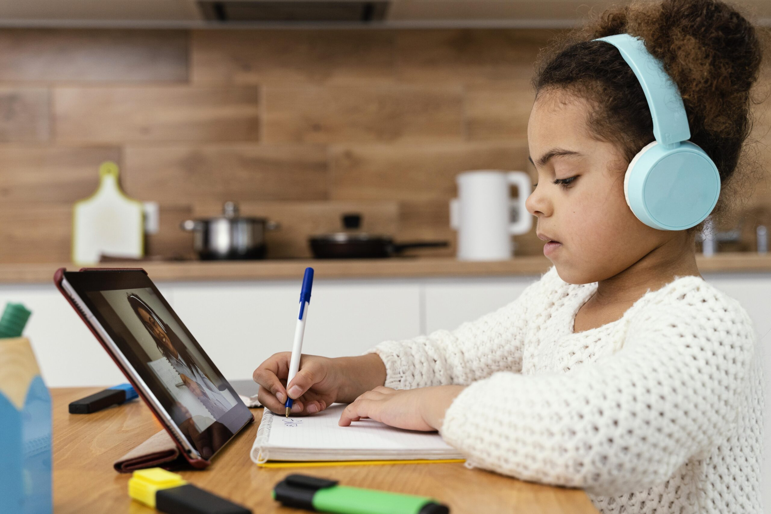 side-view-of-little-girl-during-online-school-with-tablet (1)